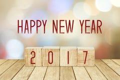 Cubos de madera con 2017 y Feliz Año Nuevo sobre backgr del bokeh de la falta de definición Imagen de archivo