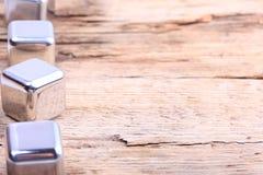 Cubos de prata de aço na superfície de madeira velha Imagem de Stock