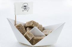 Cubos del azúcar de Brown en un barco de papel Fotografía de archivo libre de regalías