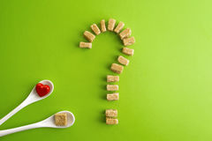 Cubos del azúcar de Brown formados como signo de interrogación sobre fondo del verdor y dos cucharas blancas con el corazón en un Fotos de archivo libres de regalías