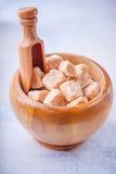 Cubos del azúcar de caña de Brown en un cuenco de madera Imagen de archivo