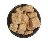 Cubos del azúcar de caña en tazón de fuente, aislados Foto de archivo libre de regalías