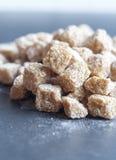 Cubos del azúcar de caña entero marrón, foco bajo Foto de archivo libre de regalías