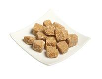 Cubos del azúcar de caña marrón en placa, aislados Fotos de archivo libres de regalías