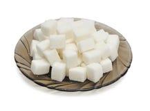 Cubos del azúcar en la placa negra Foto de archivo libre de regalías