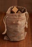 Cubos del azúcar marrón del bastón en un saco de la arpillera Fotografía de archivo