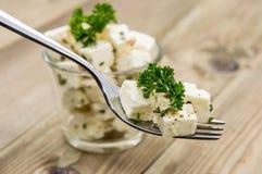 Cubos del queso feta en una fork Imágenes de archivo libres de regalías