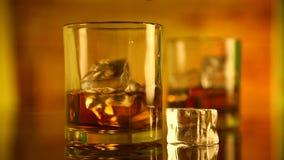 Cubos del whisky y de hielo del alcohol en un vidrio almacen de metraje de vídeo