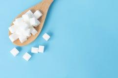 Cubos do açúcar da opinião superior do close up no backgrou azul branco da colher de madeira Foto de Stock Royalty Free