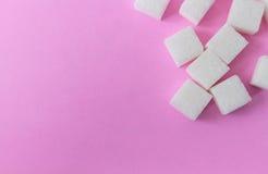 Cubos do açúcar da opinião superior do close up no fundo, no alimento e na saúde cor-de-rosa Fotografia de Stock