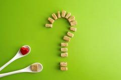 Cubos do açúcar mascavado dados forma como um ponto de interrogação sobre o fundo das hortaliças e duas colheres brancas com cora Fotos de Stock Royalty Free