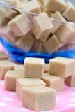 Cubos do açúcar mascavado na tabela Imagens de Stock
