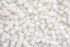 Cubos do açúcar refinado como o fundo Fotos de Stock
