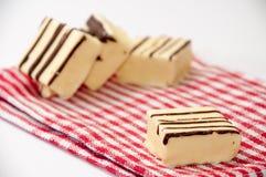 Cubos do chocolate branco em uma toalha de mesa vermelha da cozinha imagens de stock royalty free