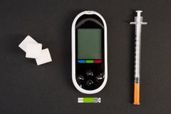 Cubos do glucometer da seringa da insulina e do açúcar branco fotografia de stock royalty free