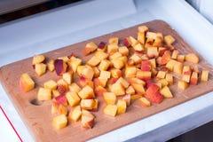Cubos dos pêssegos em uma placa de corte em um congelador Imagens de Stock Royalty Free