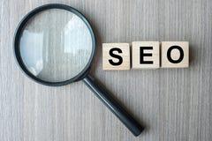 Cubos e lupa de madeira do texto de SEO Search Engine Optimization no fundo de madeira da tabela Ideia, visão, estratégia, anális foto de stock royalty free