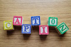 Cubos educacionais do brinquedo com as letras organizadas para indicar a palavra SUBTÍTULO - editando metadata e otimização do Se imagem de stock