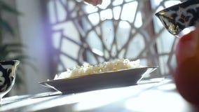 Cubos macro da carne do arroz de Pours Salt Over do cozinheiro na placa na tabela filme