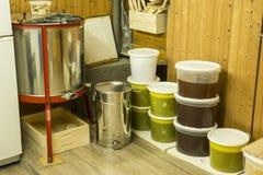 Cubos por completo de miel extraída fuera de la centrifugadora y del otro equipo del apicultor Foto de archivo