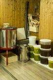 Cubos por completo de miel extraída fuera de la centrifugadora y del otro equipo del apicultor Fotografía de archivo