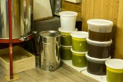 Cubos por completo de miel extraída fuera de la centrifugadora y del otro equipo del apicultor Fotos de archivo