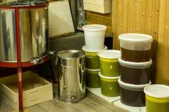 Cubos por completo de miel extraída fuera de la centrifugadora y del otro equipo del apicultor Foto de archivo libre de regalías
