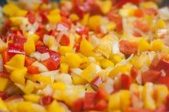 cubos rojos y amarillos de la pimienta en estufa Fotos de archivo libres de regalías