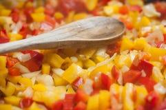 Cubos vermelhos e amarelos da pimenta no fogão com spoo de madeira Imagens de Stock Royalty Free