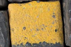 Cubos viejos o adoquines amarillos y negros del camino del granito como fondo o papel pintado Imagen vertical imagen de archivo
