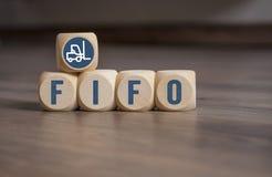 Cubos y dados con la contabilidad de LIFO y del primero en entrar, primero en salir en fondo de madera fotografía de archivo libre de regalías