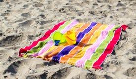 2 cubos y palas de la arena del ` s del niño en una toalla de playa rayada Imagen de archivo libre de regalías