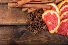 Cubra abaixo da laranja, das varas de canela e do anis de estrela frescos no fundo de madeira escuro Imagens de Stock