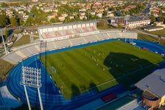 Cubra abaixo da vista ao estádio de futebol com os jogadores de futebol em Kalisz, Polônia imagem de stock