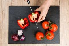 Cubra abaixo da vista na placa de corte com as mãos que cortam vegetais Foto de Stock Royalty Free
