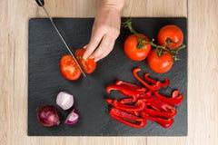 Cubra abaixo da vista na placa de corte com as mãos que cortam vegetais Imagens de Stock