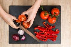 Cubra abaixo da vista na placa de corte com as mãos que cortam vegetais Fotografia de Stock Royalty Free