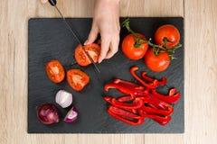 Cubra abaixo da vista na placa de corte com as mãos que cortam vegetais Imagem de Stock Royalty Free