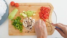 Cubra abaixo da vista na placa de desbastamento com as mãos que cortam vegetais Imagens de Stock