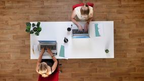 Cubra abaixo do tiro, duas fêmeas trabalhadoras que typying em seus portáteis e que sentam-se na tabela no estúdio de madeira vídeos de arquivo
