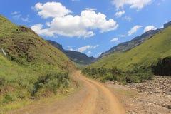 Cubra con grava el camino 4x4 que lleva con el paisaje hermoso, paso de Sani, naturaleza africana Lesotho del día de fiesta del v foto de archivo