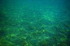 Cubra con grava la parte inferior en el mar verde fotografía de archivo