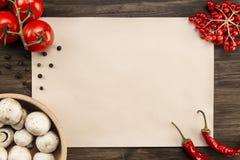 cubra el papel del vintage con los tomates, setas, pimienta de Chile en fondo de madera envejecido Alimento vegetariano sano Rece Foto de archivo