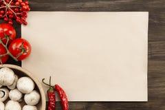 Cubra el papel viejo del vintage con los tomates, setas, pimienta de Chile en fondo de madera envejecido Alimento vegetariano san Fotografía de archivo libre de regalías