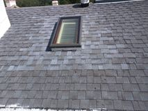 Cubra las reparaciones del escape y la instalación del tragaluz en el tejado residencial de la tabla Imagen de archivo
