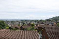 Cubra los tops del pueblo de Abergele en Gran Bretaña con el campo circundante, las montañas, las colinas y el cielo azul y las n imagen de archivo