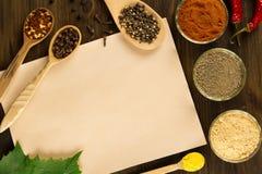 Cubra o papel velho do vintage com as especiarias no fundo de madeira Alimento saudável do vegetariano Foto de Stock