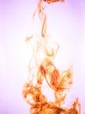 Cubra o redemoinho em uma água no fundo da cor O respingo da pintura na água Disseminação macia gotas da tinta colorida dentro fotografia de stock royalty free