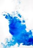 Cubra o redemoinho na água isolada no fundo branco A pintura na água Disseminação macia gotas da tinta azul dentro imagem de stock