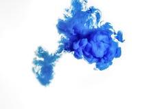 Cubra o redemoinho na água isolada no fundo branco A pintura na água Disseminação macia gotas da tinta azul dentro fotografia de stock